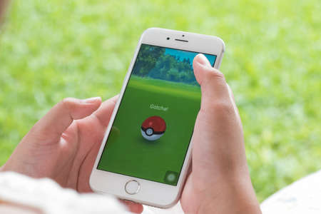 BANGKOK, THAILAND - August 6, 2016: Pokemon Go mobile game app on smart phone gadget with log in and sign up screen with pikachu & pokeball toy in hand 報道画像