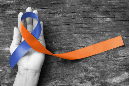 Human rights for family caregivers awareness in orange navy blue fabric ribbon color splashed on human hand old aged background