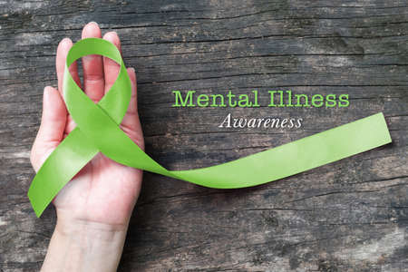 Mental illness awareness with Lime Green ribbon color on helping hand