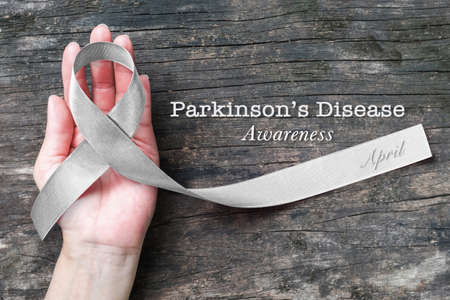Silver color ribbon on hand support for Parkinson's disease awareness and Brain cancer tumor illness