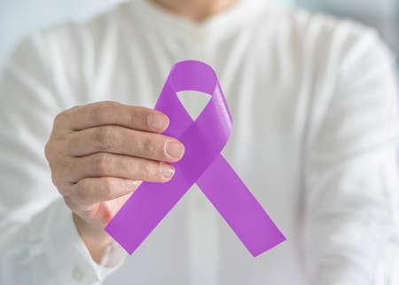 Ruban de sensibilisation au cancer violet lavande sur la main de la personne, couleur d'arc symbolique pour soutenir le patient avec toutes sortes de tumeurs, mois national des survivants du cancer et maladie de l'épilepsie Banque d'images