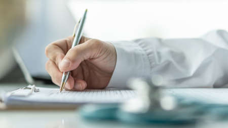 Medical doctor writing on patient personal health care record discharge form, or prescription paperwork in hospital office, clinic center for healthcare and life insurance concept