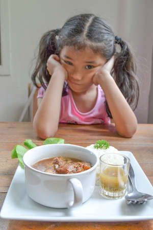 Asian kid getting bored of food refusing meal with appetite loss, no hungry eating habit (focus on food in dish) 免版税图像