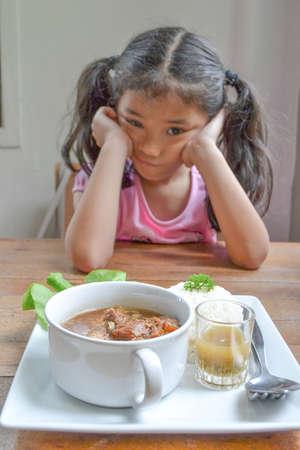 Asiatisches Kind langweilt sich von Nahrungsverweigerung mit Appetitverlust, keine hungrige Essgewohnheit (Fokus auf Essen in der Schüssel)
