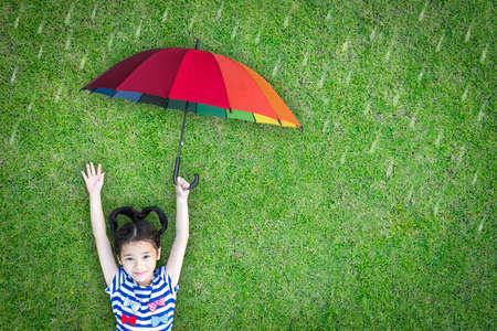 Concepto de seguro de atención médica para la protección de la salud médica de la familia y los niños, inmunización para la prevención de la gripe con una niña de la escuela asiática feliz que sostiene el paraguas bajo la lluvia en el césped verde