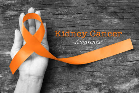 Kidney cancer awareness orange ribbon on human helping hand+ old aged background
