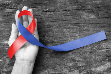Red and Blue ribbon awareness on woman human hand aged wood for Congenital Heart Defects disease