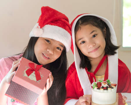 Asian kids with santa claus hat holding gift box giving present on seasonal holidays celebration
