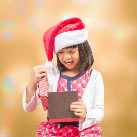 Boxing day concept with Asian girl kid with santa claus hat opening gift box with surprise