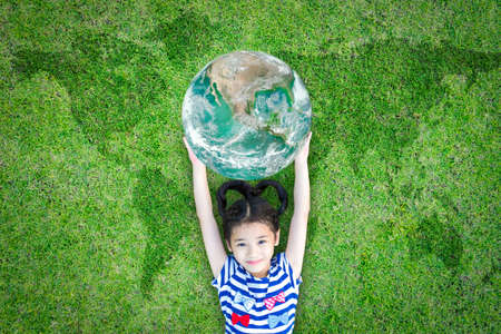 Sustainable world environment and CSR with people campaign concept with girl kid raising earth on green lawn:
