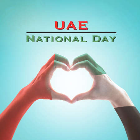 UAE, United Arab Emirate national flag pattern on people's hands in heart shape on blue mint sky background Фото со стока