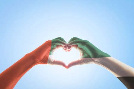 UAE, United Arab Emirate national flag pattern on people's hands in heart shape on blue mint sky background Stock Photo