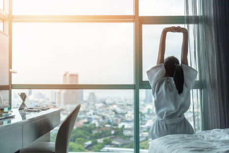 Work-life quality balance concept with happy city lifestyle Asian girl having a good day waking up from sleep in morning taking some rest, lazily relaxing in comfort in condominium or hotel bed room Archivio Fotografico - 133543900