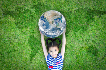Earth day, ecological friendly and corporate social responsibility concept with kid raising world on green lawn