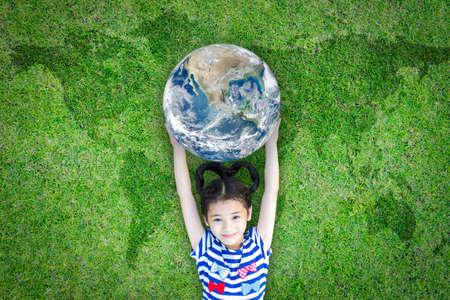 Giornata della Terra, concetto ecologico e di responsabilità sociale delle imprese con il mondo che alleva bambini sul prato verde