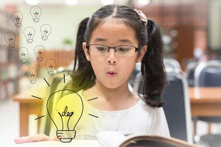 Idea creativa innovadora para el concepto de ley de derechos de autor con un niño sorprendido leyendo un libro con una bombilla en la biblioteca Foto de archivo