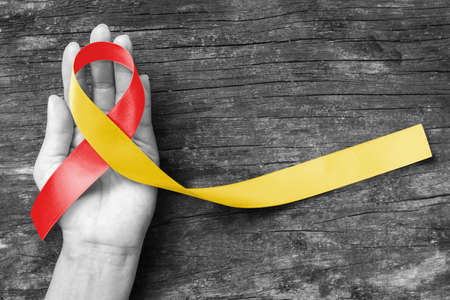 World hepatitis day and HIV/ HCV co-infection awareness with red yellow ribbon  on person's hand support and old aged wood