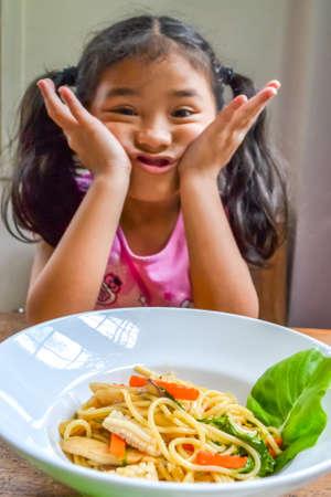 Niño asiático aburrido de la comida rechazando la comida con pérdida de apetito, sin hábito de comer hambriento Foto de archivo