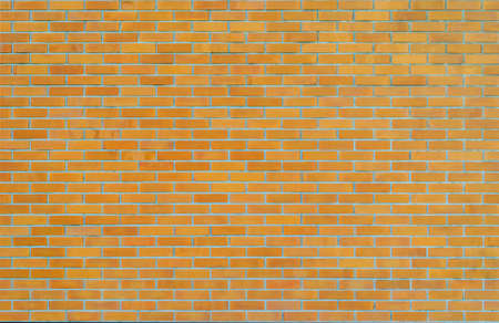 Brick wall texture background in yellow brown tone Фото со стока