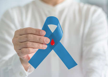 Diabetes Awareness ribbon for World diabetes day with red blood drop on blue bow color in person hand for supporting patient with diabetic disease Reklamní fotografie