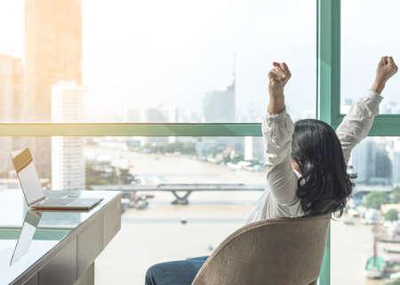 Erledigte Arbeit, Lebensbalance und Erfolgsfeierkonzept mit glücklicher Frau machen es sich leicht, sich im Luxus-Business-Hotel oder am Home-Office-Arbeitsplatz mit Computer-PC-Laptop auf dem Schreibtisch auszuruhen Standard-Bild