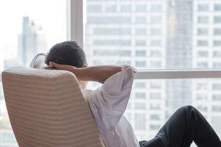 Life-Work-Balance und Lifestyle-Konzept für das Leben in der Stadt von Geschäftsmann, der sich entspannt, entspannen Sie sich im Büroraum und denken Sie nachdenklich an Lifestyle-Qualität, die sich auf die städtische Szene freut