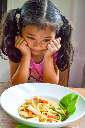 Asian kid getting bored of food refusing meal with appetite loss, no hungry eating habit