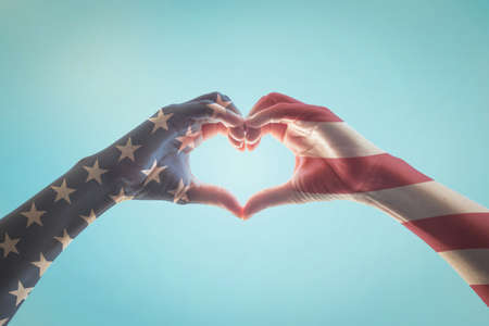 United States of America -USA American flag pattern on people hands in heart love shape isolated on blue sky background