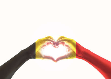 Belgian black yellow red flag pattern on people heart shaped hands (clipping path) on white background