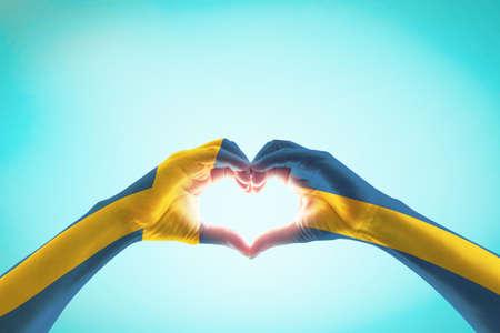Sweden flag on people heart shape hands.