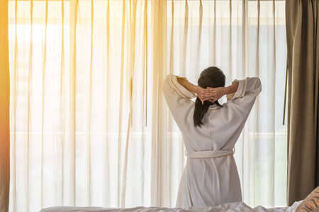 Easy lifestyle Asian woman waking up in the morning taking some rest relaxing in hotel room Banco de Imagens