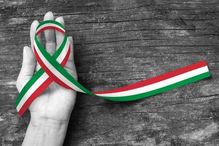 Patrón de cinta de color de la bandera nacional de Italia en la mano de la gente (aislada con trazado de recorte) para el apoyo italiano o nacional y el recuerdo del festival navideño Foto de archivo