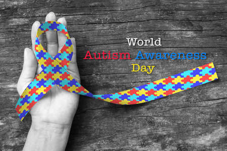 World Autism awareness day with Puzzle ribbon on persons hand