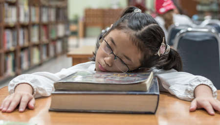 School student fall asleep while reading book in library or class from overwhelming learning or studying hard for exam, effecting kid health