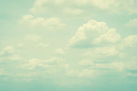Vintage style sky with soft clouds in cool cyan color on watercolor paper textured background