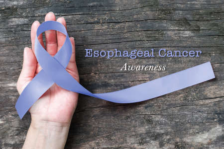 Esophageal cancer awareness Periwinkle color ribbon on human hand with aged wood background