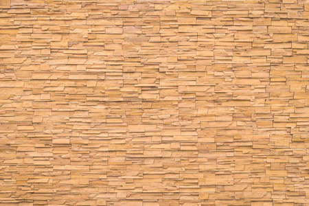 Yellow orange brown rock stone brick tile wall aged texture detailed pattern background