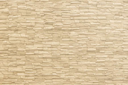 Rock stone brick tile wall aged texture detailed pattern background in yellow cream beige color  版權商用圖片