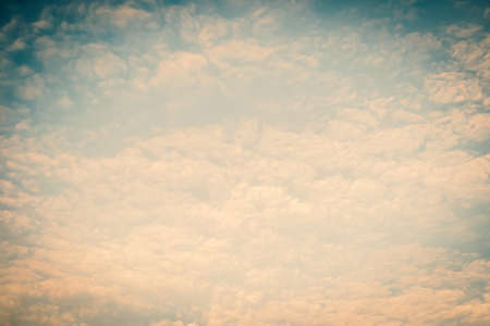 Blurred nature background of scattered clouds on sky in cool vintage color