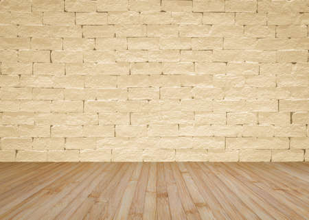 Grunge brick wall painted in light yellow beige with wooden floor in natural brown for interior backgrounds