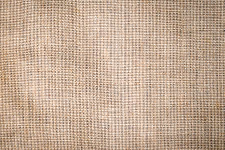 Hessian sackcloth woven texture pattern background in light sepia tan beige cream brown color