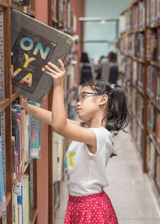Student girl kid in school library selecting books for reading in class room from bookshelf