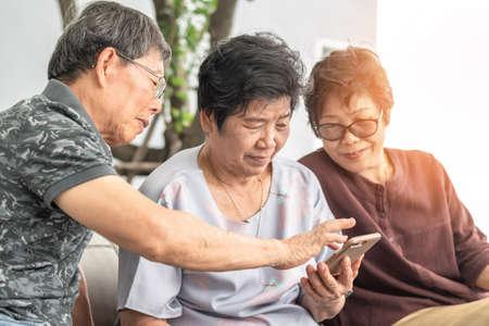 Elderly senior woman and aged man lifestyle learning using mobile phone and digital internet technology reading e-book, social media network Reklamní fotografie