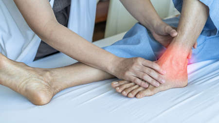 Ankle pain from instability, arthritis, gout, tendonitis, fracture, nerve compression (tarsal tunnel syndrome), infection and poor structural alignment of leg or foot in ageing patient with doctor Reklamní fotografie - 142233421