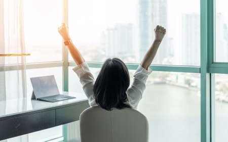 Business achievement concept with happy businesswoman relaxing in office or hotel room, resting and raising fists with ambition looking forward to city building urban scene through glass window Reklamní fotografie - 142933749