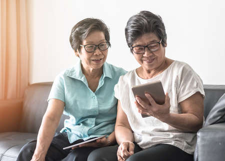 Aging society concept with Asian elderly senior adult women (twin sisters) using mobile tablet application technology for social network among friends community via internet digital communication