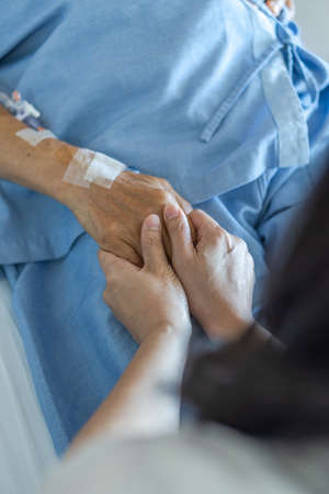 Caregiver holding elderly senior patient (ageing old adult person) hand in hospital bed or nursing hospice, geriatrician palliative home, while caretaker having  medical health care service