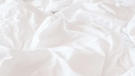 White bed sheet blanket, wrinkled duvet, crumpled comforter cloth used in hotel, resort or home interior for bedding background and sleep comfort Imagens