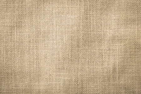 Hessian sackcloth woven texture pattern background in light cream yellow beige