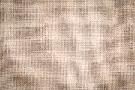 Hessian sackcloth woven texture pattern background in tan sepia beige cream brown color